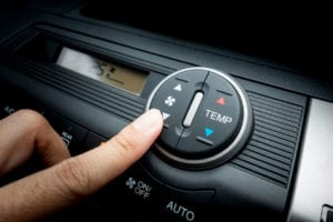 Finger pressing on Fan switch of a Car air conditioning system